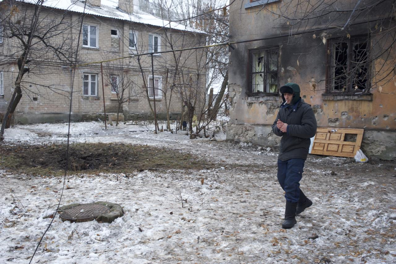 A man walks past a mortar impact site outside a damaged building in Donetsk, eastern Ukraine, Tuesday, Dec. 9, 2014. Government troops and Russian-backed separatists largely suspended hostilities in east Ukraine Tuesday in a fresh attempt to revive a largely ignored cease-fire deal. (AP Photo/Balint Szlanko)