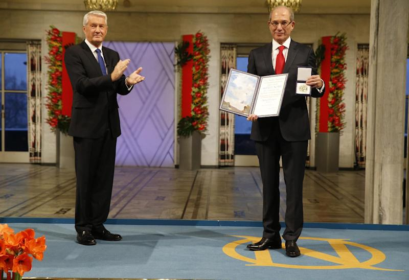 Ahmet Uzumcu, right, Director General of the Organization for the Prohibition of Chemical Weapons receives the Nobel Peace Prize from Chairman of the Norwegian Nobel Committee Thorbjorn Jagland in City Hall Oslo Tuesday Dec. 10, 2013. The OPCW received the 2013 Peace Nobel Prize for its extensive efforts to eliminate chemical weapons. (AP Photo/Cornelius Poppe / NTB scanpix) NORWAY OUT