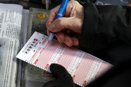 File Phot0: A woman fills out a ticket for the $700 million Powerball lottery draw at Times Square in the Manhattan borough of New York