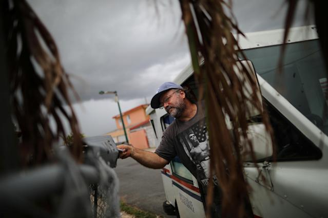 <p>Alfredo Martinez, a mail man for the U.S. Postal Service delivers the mail at an area damaged by Hurricane Maria in San Juan, Puerto Rico, Oct. 6, 2017. (Photo: Carlos Barria/Reuters) </p>