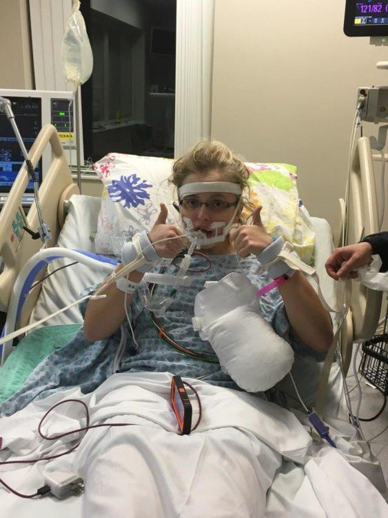the author in a hospital bed with many wires and tubes connected to her, holding her thumbs up