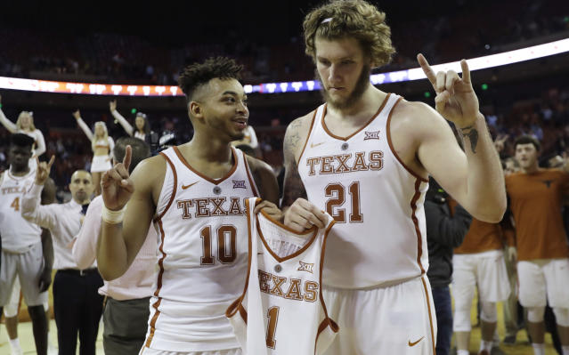 FILE - In this Jan. 10, 2018, file photo, Texas guard Eric Davis Jr. (10) and forward Dylan Osetkowski (21) hold the jersey of teammate Andrew Jones (1) during the school song following an NCAA college basketball game against TCU, in Austin, Texas. Jones, diagnosed with leukemia, was the emotional core in a season-long struggle to get back to the tournament after missing last year. (AP Photo/Eric Gay, File)
