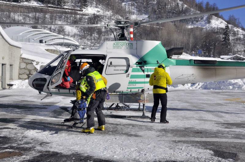Rescuers prepare to board an helicopter in Aosta, Italy, Monday, Feb. 4, 2019, to reach the spot where the bodies of three skiers where found. Rescuers have found the bodies of three skiers in Italy's Alps and are searching for a fourth, raising the death toll in recent avalanches in the country to at least five. The Valdostano Alpine Rescue aircraft on Monday, searching for two British and two French skiers who were reported missing a day earlier, spotted three bodies. Dogs were helping in the search. (Thierry Pronesti/ANSA Via AP)
