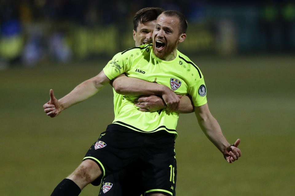 In this photo taken on Saturday, March 28, 2020, Shakhter's Sergei Balanovich, foreground, and his teammate Azdren Llullaku celebrate after scoring their side's goal during the Belarus Championship soccer match between Gorodeya and Shakhter in the town of Gorodeya, Belarus. Longtime Belarus President Alexander Lukashenko is proudly keeping soccer and hockey arenas open even though most sports around the world have shut down because of the coronavirus pandemic. The new coronavirus causes mild or moderate symptoms for most people, but for some, especially older adults and people with existing health problems, it can cause more severe illness or death. (AP Photo/Sergei Grits)