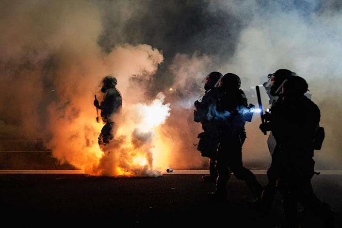 Oregon law enforcement officers wearing anti-riot gear march toward protesters through tear gas smoke on the 100th night of protests against racism and brutality in Portland, on Sept. 5.