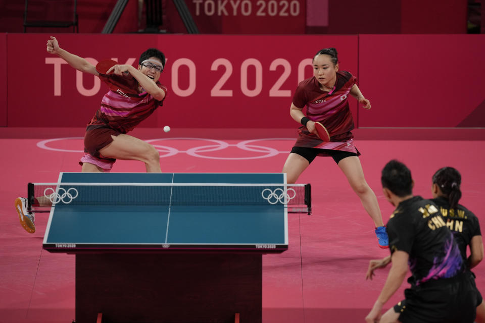 Japan's Mima Ito, left, and Jun Mizutani compete during the table tennis mixed doubles gold medal match against China's Xu Xin and Liu Shiwen at the 2020 Summer Olympics, Monday, July 26, 2021, in Tokyo. (AP Photo/Kin Cheung)