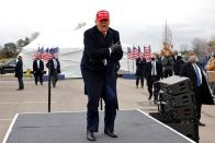 U.S. President Donald Trump reacts to cold weather and wind during a campaign rally at Michigan Sports Stars Park in Washington