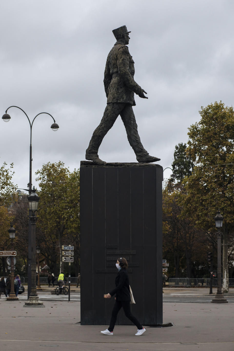 A woman wearing a mask walks by a General de Gaulle statue, on the Champs Elysees avenue in Paris, Sunday Oct.25, 2020. A curfew intended to curb the spiraling spread of the coronavirus, has been imposed in many regions of France including Paris and its suburbs. (AP Photo/Lewis Joly)