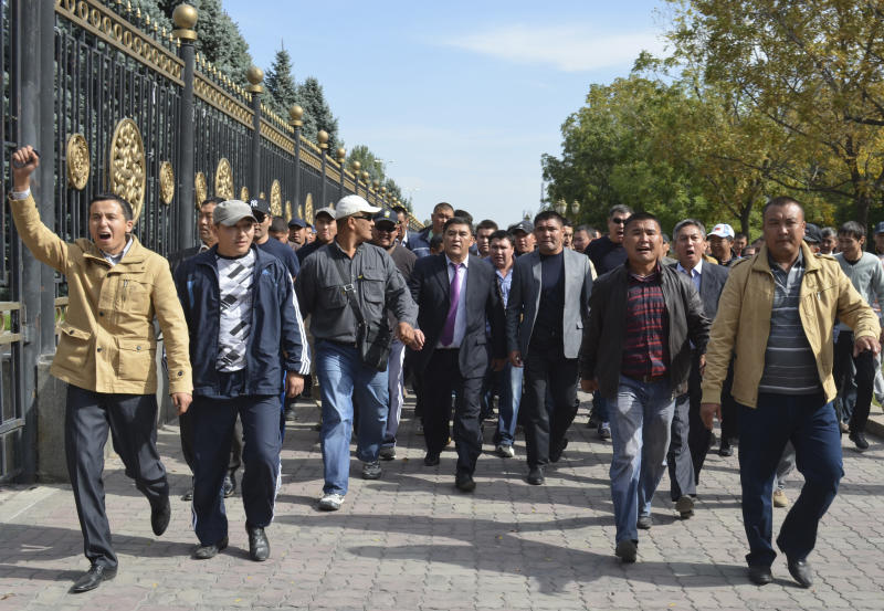 Kamchibek Tashiyev, center, surrounded by supporters, walks along a fence surrounding government headquarters in downtown Bishkek, Kyrgyz capital on Wednesday, Oct. 3, 2012. Around 1,000 people gathered in the center of the city for a rally, organized by nationalist politicians Sapar Zhaparov and Kamchibek Tashiyev, ostensibly to demand the nationalization of a controversial gold mine in the east of the Central Asian nation. Police officers protecting the government building, known as the White House, used dogs and smoke bombs to disperse a group of young men who attempted to scale the gates. (AP Photo/ Abylay Saralayev)