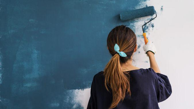 Young asian happy woman painting interior wall with paint roller in new house.