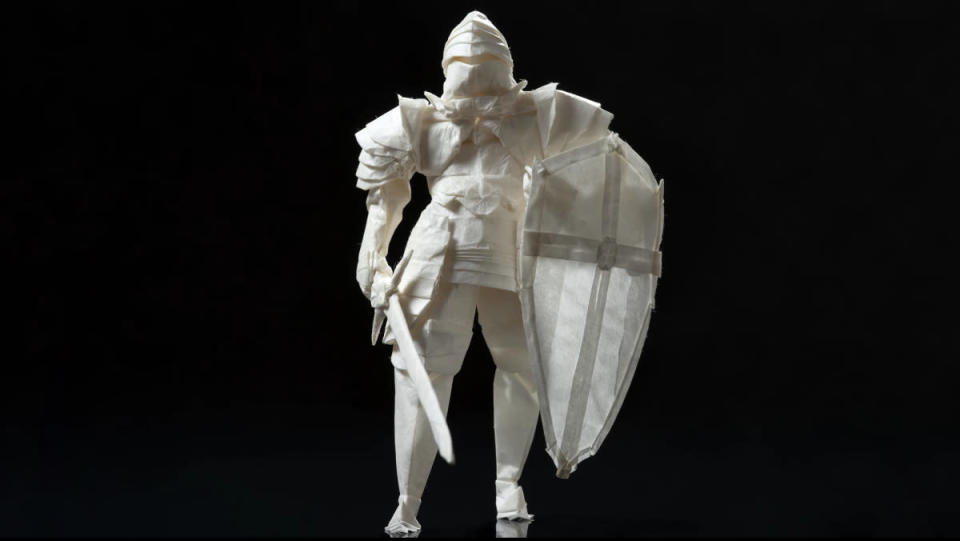 An origami knight made of rice paper with a shield and sword stands in front of a pure-black background.