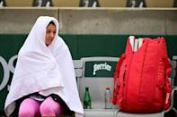 Cover-up: Russia's Margarita Gasparyan waits for the rain to stop