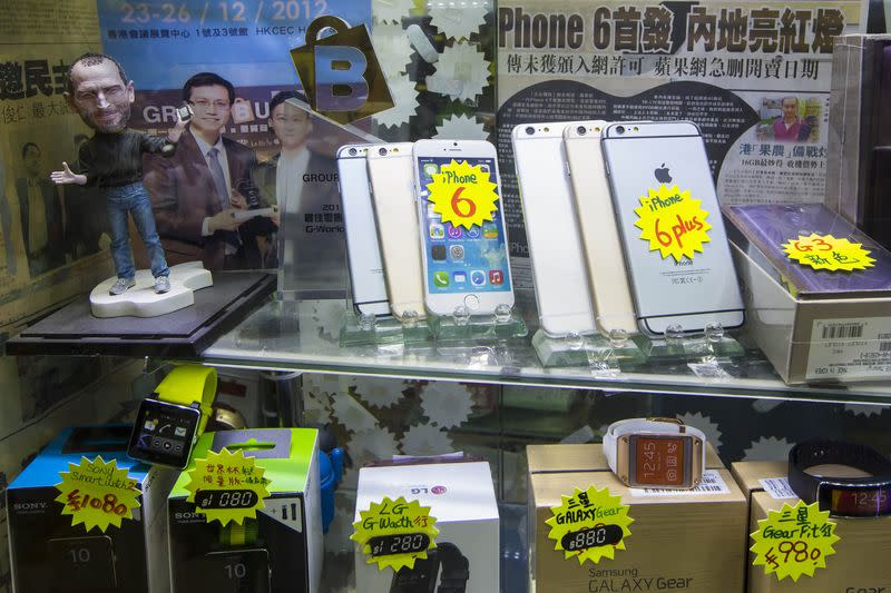 Dummies of new Apple iPhone 6 and 6 Plus are displayed with a figure of the late Apple founder Steve Jobs at a mall selling smartphones in Hong Kong