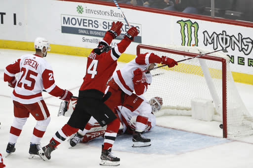CORRECTS TO GOAL BY ANDY GREENE MOT WAYNE SIMMONDS - New Jersey Devils left wing Miles Wood (44) celebrates as a shot by Andy Greene (not shown) goes into the net behind Detroit Red Wings goaltender Jonathan Bernier (45) as Red Wings defenseman Mike Green (25) watches during the third period of an NHL hockey game, Thursday, Feb. 13, 2020, in Newark, N.J. (AP Photo/Kathy Willens)