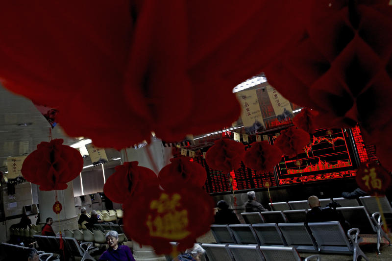Investors monitor stock prices at a brokerage house decorated with red lanterns in Beijing, Friday, Feb. 1, 2019. Asian markets were mixed on Friday as trade talks ended in Washington with no deal but the promise of a second meeting between U.S. President Donald Trump and Chinese leader Xi Jinping. Gains were limited by a private survey showing that Chinese manufacturing slowed to the lowest level in almost three years. (AP Photo/Andy Wong)