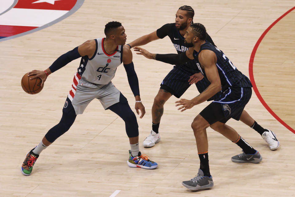 Washington Wizards guard Russell Westbrook (4) holds the ball as Orlando Magic guard Michael Carter-Williams (7) and center Khem Birch (24) defend in the second quarter of an NBA basketball game Saturday, Dec. 26, 2020, in Washington. (Geoff Burke/Pool Photo via AP)
