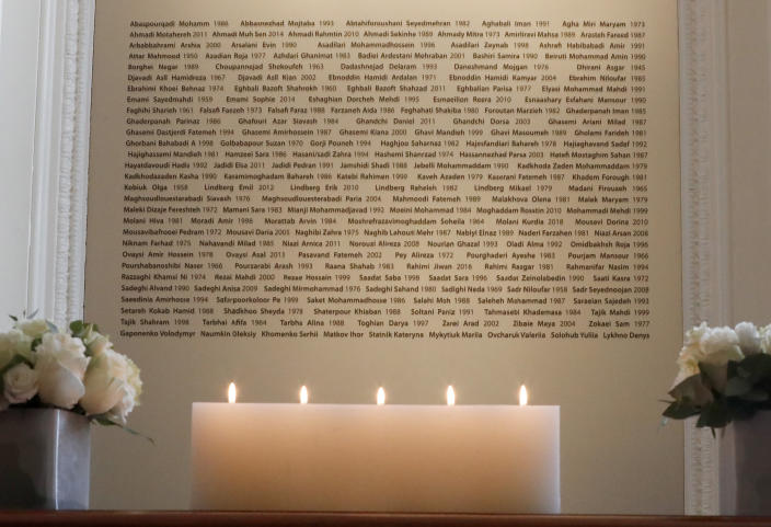 Candles burn in front of a plaque with the names of the victims of flight PS752, at the High Commission of Canada in London, Thursday, Jan. 16, 2020. The Foreign ministers gather in a meeting of the International Coordination and Response Group for the families of the victims of PS752 flight crashed shortly after taking off from the Iranian capital Tehran on Jan. 8, killing all 176 passengers and crew on board. (AP Photo/Frank Augstein)