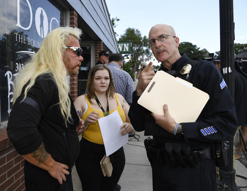 "EDGEWATER , CO - AUGUST 02: Duane ""u201cDog The Bounty Hunter""u201d Chapman, left, and his daughter, Bonnie Jo Chapman, center, talks with Edgewater Police corporal Robert Brink before Chapman's press conference in front of his store August 02, 2019. The store, which sells apparel and merchandise from his reality television show, was burglarized on Tuesday, some of his late wife's belongings were stolen along with other items. Beth Chapman died in June of cancer. Dog Chapman offered not to press charges if the suspect came forward in 48 hours. (Photo by Andy Cross/MediaNews Group/The Denver Post via Getty Images)"