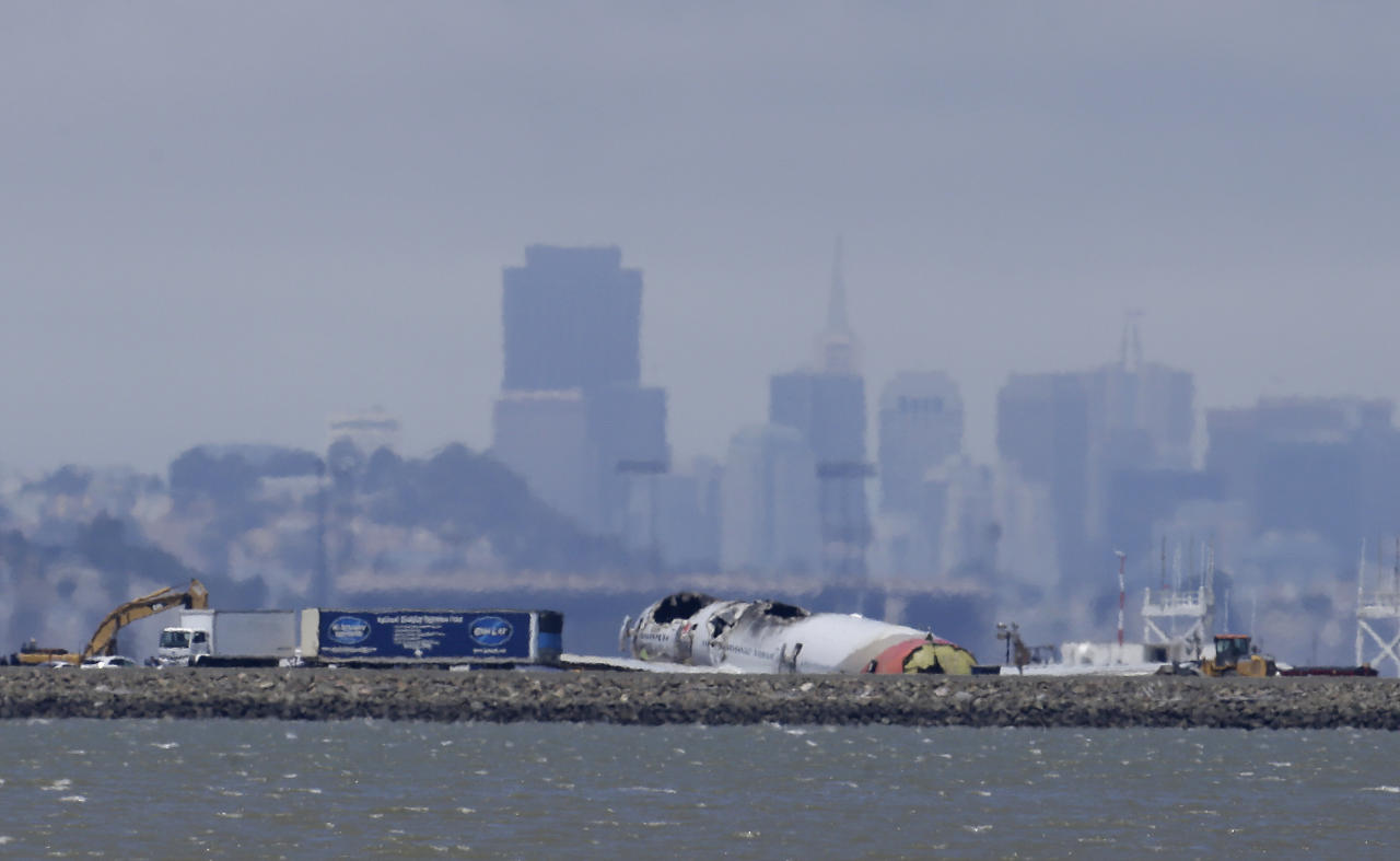 The wreckage of Asiana Flight 214 sits on a tarmac at San Francisco International Airport in San Francisco, Thursday, July 11, 2013. Asiana Airlines Flight 214 from Shanghai and Seoul crash-landed July 6, 2013, when it came in too low and too slow, killing two Chinese passengers and injuring many others as it skidded and spun 100 feet (30 meters). Most of the injured suffered minor injuries. (AP Photo/Jeff Chiu)