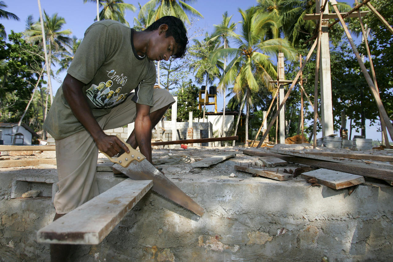 UNAWATUNA, SRI LANKA - DECEMBER 23: A Sri Lankan construction worker cuts a piece of wood helping to  build the new Comara Beach Club on the beach on December 23, 2005 in Unawatuna, Sri Lanka. Tourists are coming back slowly to the region which was devastated on December 26, 2004 by the tsunami, but the numbers are considered lower than in previous years.  (Photo by Paula Bronstein /Getty Images)