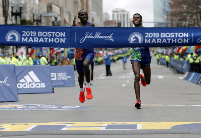 FILE - In this April 15, 2019, file photo, Lawrence Cherono, left, of Kenya, runs to the finish line to win the 123rd Boston Marathon in front of Lelisa Desisa, of Ethiopia, right, in Boston. The Boston Marathon is offering refunds for the first time because of the new coronavirus pandemic. Race organizers say anyone who was entered in the 124th edition of the race this month can still run on the rescheduled date, Sept. 14. But if they cant make it, they can have their money back. (AP Photo/Winslow Townson, File)