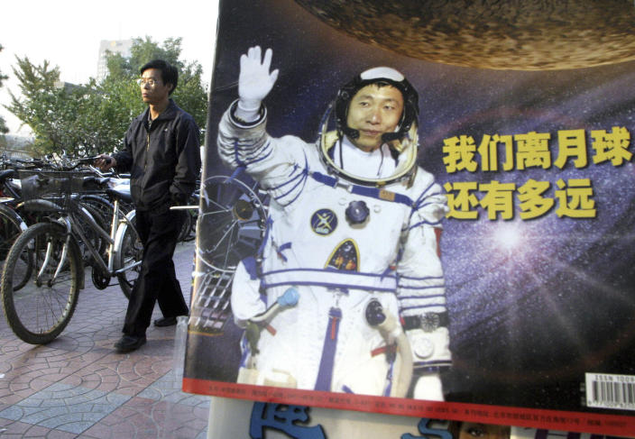 """In this photo taken Thursday, Oct 23, 2003, a man pushes his bicycle past the cover of a magazine showing China's first man in space, Yang Liwei and the Chinese characters for """"How far are we from the moon?"""" at a newsstand in Beijing, China. China's Nov. 24, 2020, trip to the moon and, presumably, back is the latest milestone in the Asian powerhouse's slow but steady ascent to the stars. (AP Photo/Ng Han Guan, File)"""
