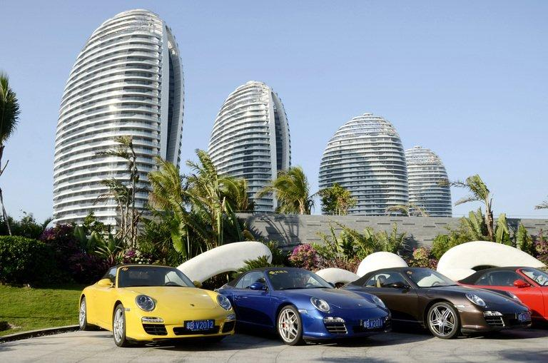 Sports cars parked in front of luxury apartment blocks at Phoenix Island, in the Chinese seaside city of Sanya, on January 19, 2013. Chinese manufacturers once snapped up luxury apartments on Phoenix Island, but with profits falling as a result of the global downturn many owners need to offload properties urgently and raise cash to repay business loans, estate agents said