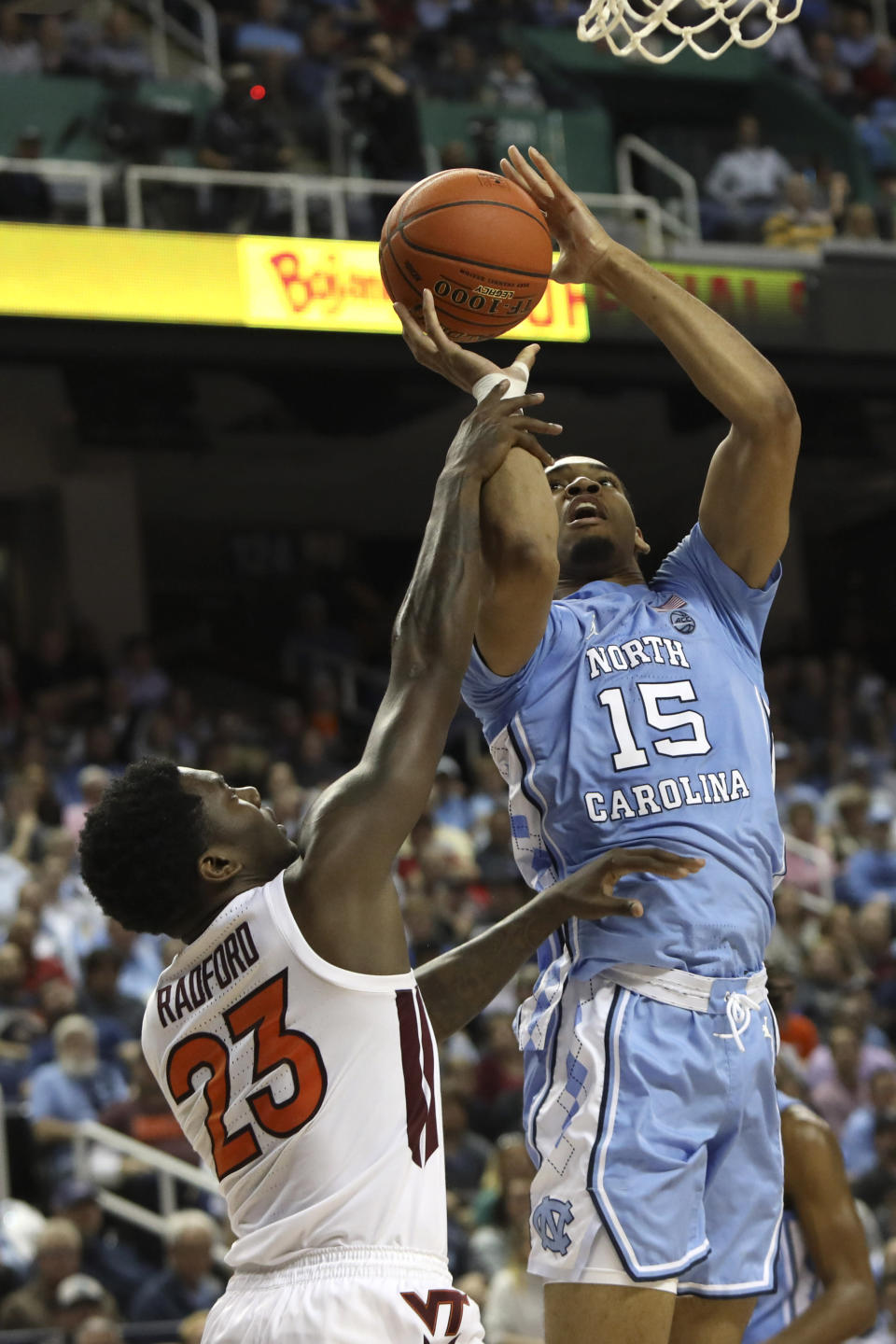 Virginia Tech guard Tyrece Radford (23) defends while North Carolina forward Garrison Brooks (15) shoots during the first half of an NCAA college basketball game at the Atlantic Coast Conference tournament in Greensboro, N.C., Tuesday, March 10, 2020. (AP Photo/Ben McKeown)