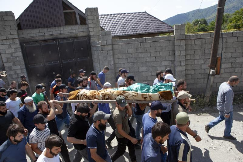 FILE-In this Aug. 29, 2019 file photo people carry the body of the victim who has been identified as Zelimkhan Khangoshvili, a Georgian Muslim during the funeral in Duisi village, the Pankisi Gorge valley, in Georgia. Germany's foreign ministry says it has expelled two Russian diplomats after prosecutors announced they suspected Moscow's involvement in the brazen daylight slaying of a Georgian man in Berlin. (AP Photo/Zurab Tsertsvadze)