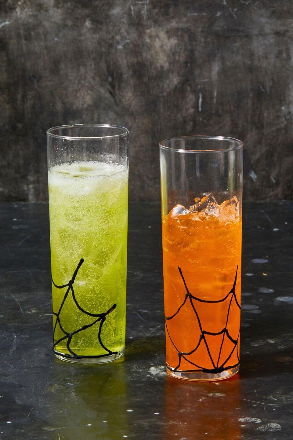 <p>Give plastic or glass tumblers a Halloween makeover by drawing spider web patterns with puff paint. Serve neon-colored drinks, like orange soda, for a pop of color.</p>