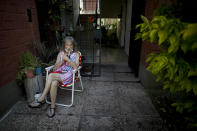 """Carmela Corleto drinks mate outside her home where she lives alone and waits for her turn for the COVID-19 vaccine in Burzaco, Argentina, Thursday, Feb. 25, 2021. Corleto, who said that the vaccine is like the light at the end of the tunnel in Ernesto Sabato's book titled """"The tunnel,"""" got her first shot of the AstraZeneca vaccine on April 23, 2021, (AP Photo/Natacha Pisarenko)"""