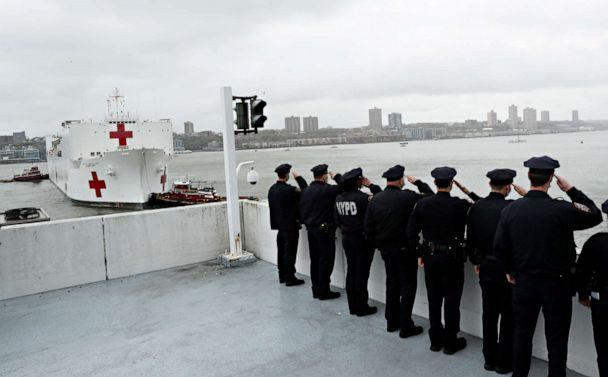 PHOTO: Police officers salute as the U.S. Navy hospital ship USNS Comfort as it departs Pier 90 in Manhattan under thick fog to return to its home port of Norfolk, Va., April 30, 2020. (Lucas Jackson/Reuters)