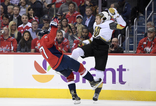 Washington Capitals right wing T.J. Oshie, left, collides with Vegas Golden Knights defenseman Jon Merrill during the second period of an NHL hockey game Wednesday, Oct. 10, 2018, in Washington. (AP Photo/Nick Wass)