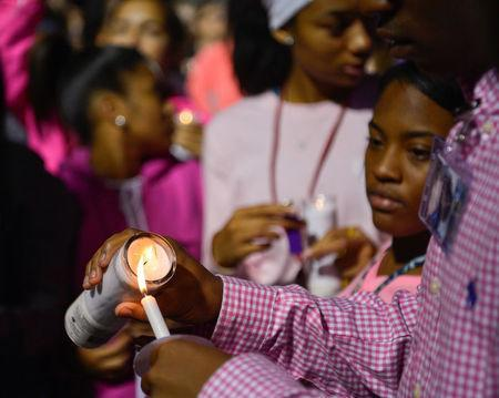 People gather during a candlelight vigil at Lafayette High School for Trinity Gay, the daughter of Olympic sprinter Tyson Gay, who died in an exchange of gunfire early Sunday morning, in Lexington, Kentucky, October 17, 2016. REUTERS/Bryan Woolston