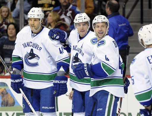 Vancouver Canucks defenseman Andrew Alberts, left, center Alex Burrows, center, and defenseman Keith Ballard, right, celebrate Burrows' goal in the second period of an NHL hockey game against the Colorado Avalanche, Sunday, March 24, 2013, in Denver. (AP Photo/Chris Schneider)