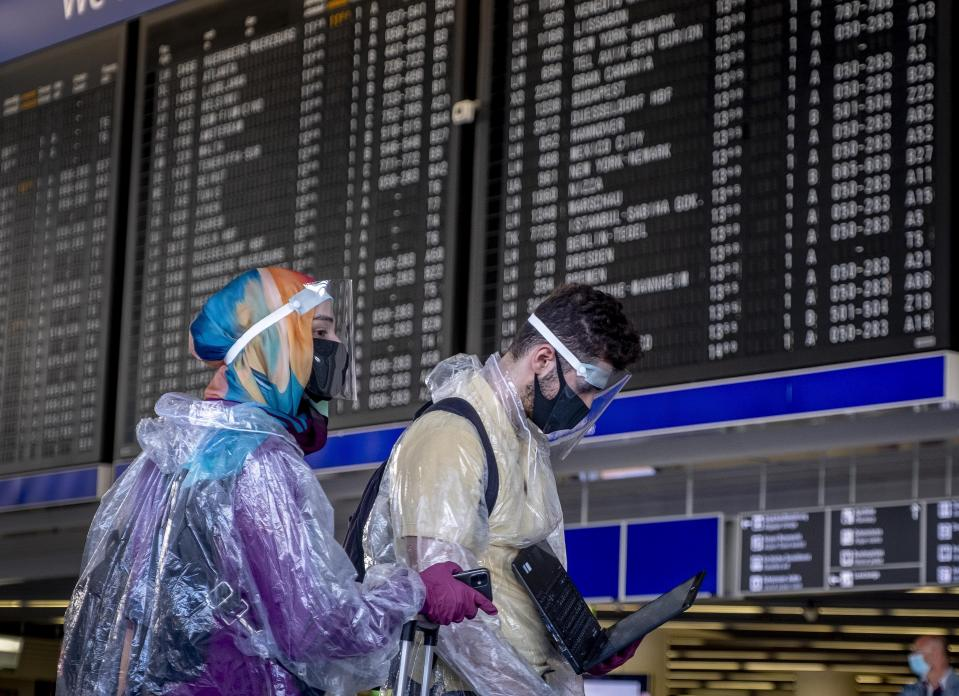 Passengers with protection gear walk past the flight board at the airport in Frankfurt, Germany, Friday, July 24, 2020. (AP Photo/Michael Probst)