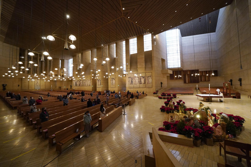 Worshipers gather for Christmas Eve Mass inside the Cathedral of Our Lady of the Angels Thursday, Dec 24, 2020, in Los Angeles. California became the first state to record 2 million confirmed coronavirus cases, reaching the milestone on Christmas Eve as nearly the entire state was under a strict stay-at-home order and hospitals were flooded with the largest crush of cases since the pandemic began. (AP Photo/Ashley Landis)