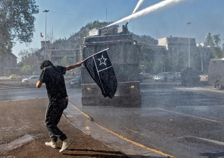 A demonstrator is sprayed by water cannon during a protest against President Sebastian Pinera's government in Santiago ahead of Sunday's referendum
