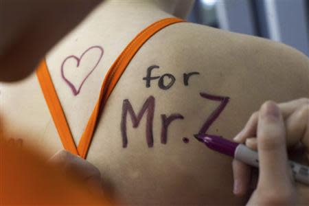 Eastside Catholic Middle School student Sarah Merlino gets a message of support written on her back for former Vice Principal and swimming coach Mark Zmuda during a swim meet at Rainier Beach Pool in Seattle, Washington, December 20, 2013. REUTERS/David Ryder