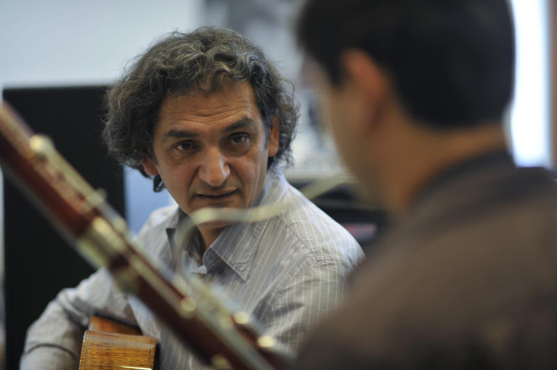FILE - In this March 14, 2012 file photo, Ferenc Snetberger, guitarist and founder of the Snetberger Music Talent Center teaches in his school in Felsoors, Hungary. Hungarian guitarist Ferenc Snetberger is giving dozens of young Roma musicians a unique opportunity to learn in the Snetberger Music Talent Center. (AP Photo/Bela Szandelszky, File)