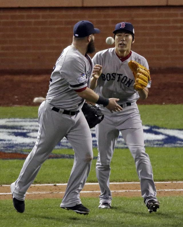 Boston Red Sox first baseman Mike Napoli tosses the game ball to relief pitcher Koji Uehara (19) after Boston defeated the St. Louis Cardinals, 4-2, in Game 4 of baseball's World Series Sunday, Oct. 27, 2013, in St. Louis. (AP Photo/Charlie Riedel)