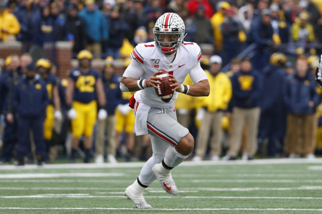 """Ohio State quarterback <a class=""""link rapid-noclick-resp"""" href=""""/ncaaf/players/287612/"""" data-ylk=""""slk:Justin Fields"""">Justin Fields</a> (1) rolls out to throw against Michigan in the first half of an NCAA college football game in Ann Arbor, Mich., Saturday, Nov. 30, 2019. (AP Photo/Paul Sancya)"""