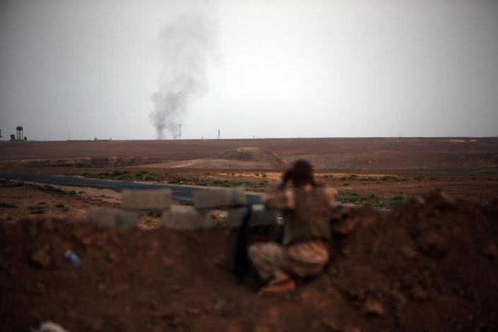 A Peshmerga fighter looks at smoke rising in the horizon on the front line of battles with Islamic State militants east of Mosul, on August 18, 2014 (AFP Photo/Ahmad al-Rubaye)