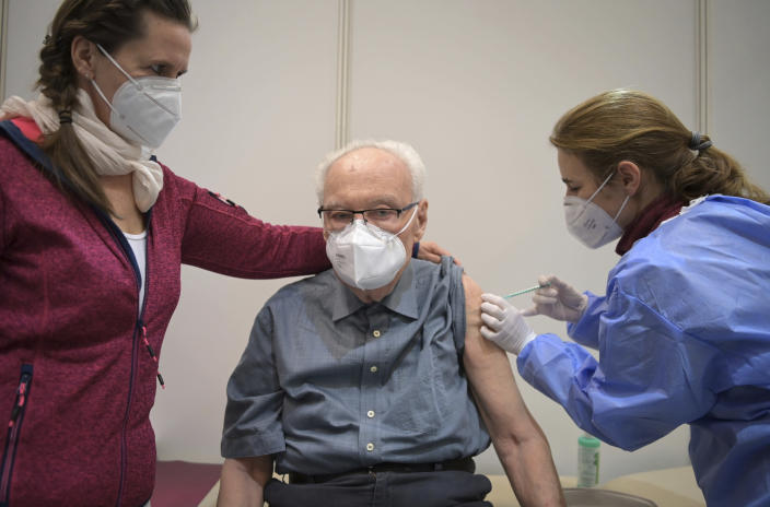 Werner Boestfleisch, center, is being vaccinated against Corona by doctor Conny Mauruschat, right, assisted by nurse Peggy, in the newly opened Centre for Corona Vaccination in the Metropolishalle of the Babelsberg Film Park in Potsdam, Germany, Tuesday, Jan. 5, 2021. (Soeren Stache/POOL via AP)