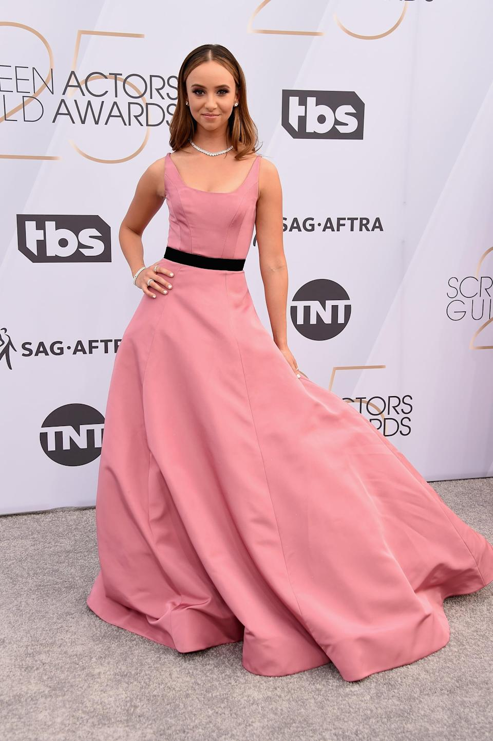 <p>Wearing a light pink gown with a black slash around the waist and Hearts On Fire jewels and Stuart Weitzman heels.</p>