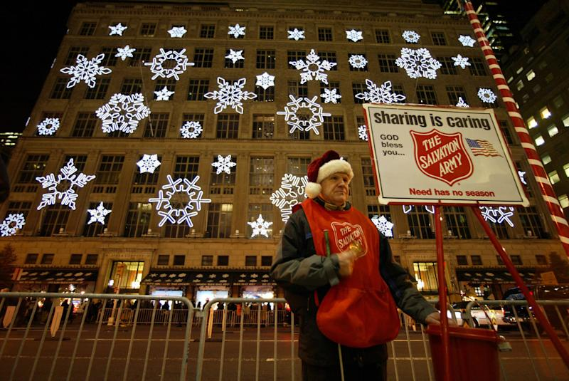 Reed Devlin, a blind Salvation Army volunteer, rings his bell across the street from the holiday windows and snow flake light show of Saks Fifth Avenue Monday, Dec. 13, 2004. Each holiday season the stores in midtown Manhattan try to out do each other in creating the most original displays to attract visitors from around the country and the world - and their money. (AP Photo/Mary Altaffer)