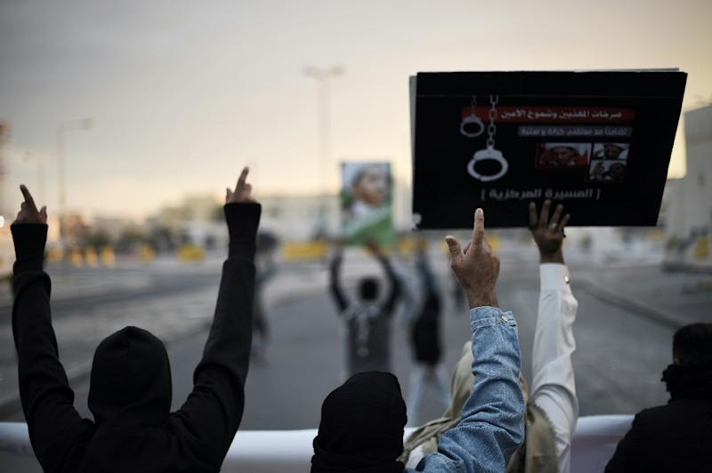 Bahraini protestors hold up placards depicting portraits of Sheikh Ali Salman, head of the Shiite opposition movement al-Wefaq, during clashes with riot police in the village of Sitra, south of the capital Manama, on January 29, 2016