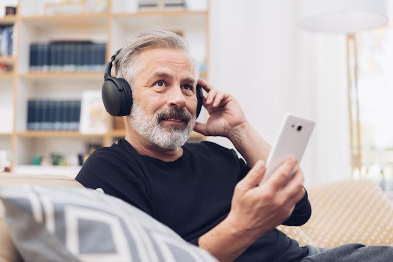 Portrait of a middle-aged man using his mobile phone for listening to music online through modern headphones at home