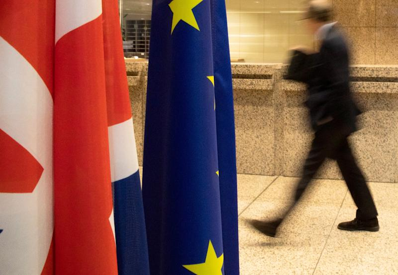 A man walks by the Union Flag and the EU flag inside the European Council building in Brussels: AP