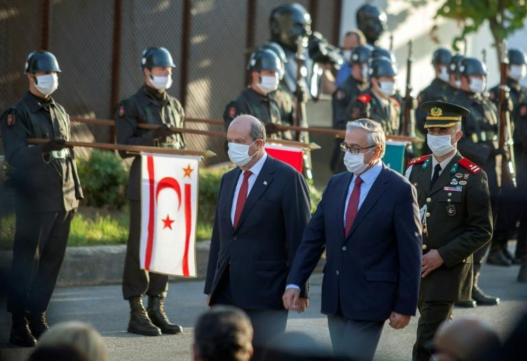 Outgoing Turkish-Cypriot leader Mustafa Akinci (R) and the newly elected leader Ersin Tatar arrive at a handover ceremony in the self-proclaimed Turkish Republic of Northern Cyprus (TRNC) for a handover ceremony
